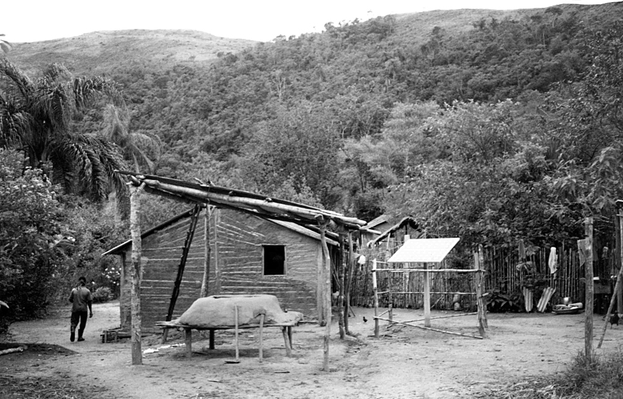 A fotografia de 1997, mostra uma casa em taipa de mão. Em primeiro plano, vê-se um fogão externo, coberto. Ao lado direito, mais ao fundo, um painel solar instalado por um programa estatal. A partir de Iporanga, chega-se ao lugar denominado Praia Grande subindo pelo rio Ribeira, único acesso até então. Imagem: Silvio Luiz Cordeiro.