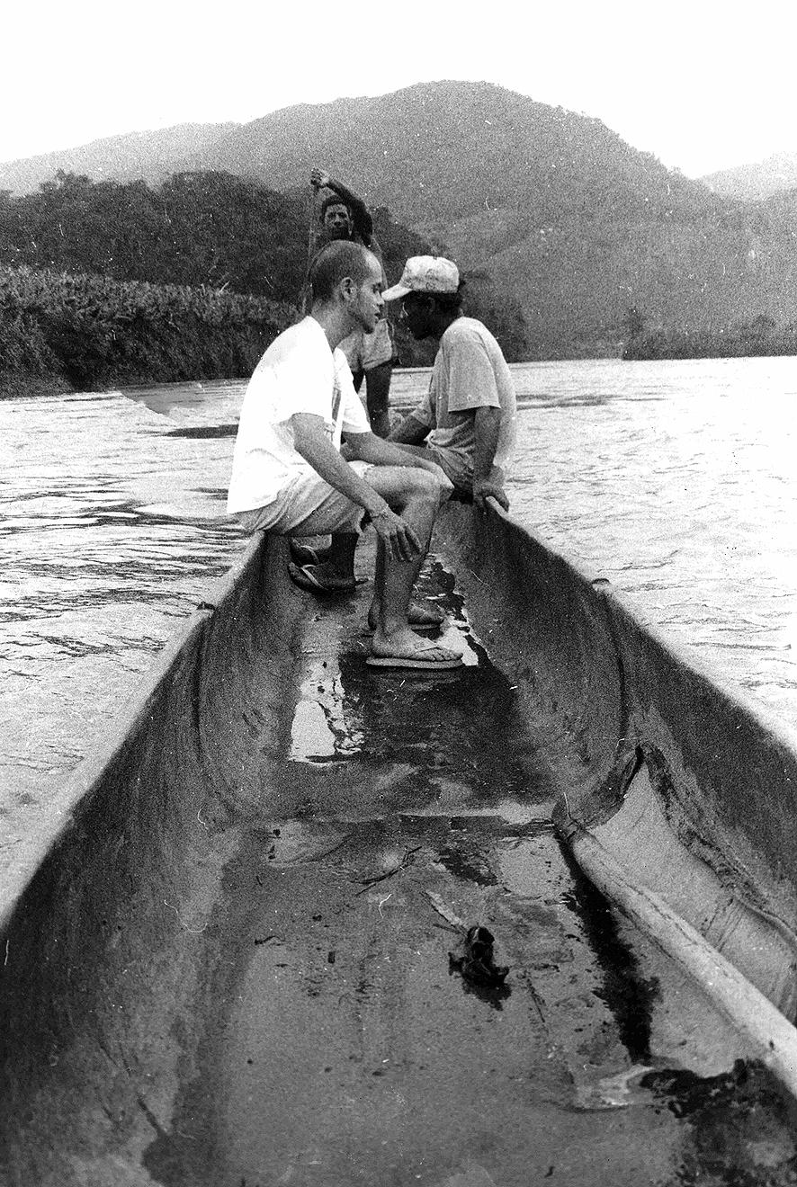 A fotografia mostra a travessia do rio Ribeira, durante uma das viagens ao vale, para estudar o habitat das antigas comunidades. Aqui, para se chegar a Ivaporunduva em 1994, a partir da margem direita do rio, acenava-se até que algum morador da comunidade quilombola, situada a frente, na margem oposta, viesse com uma canoa a remo, esculpida num tronco de árvore (Guapuruvu). Embarcava-se. E, assim, o canoeiro atravessava novamente o rio, levando ao povoado, sejam os moradores, sejam os poucos visitantes, a exemplo de Silvio Cordeiro, na borda da grande canoa. Imagem: Luciana Siqueira.