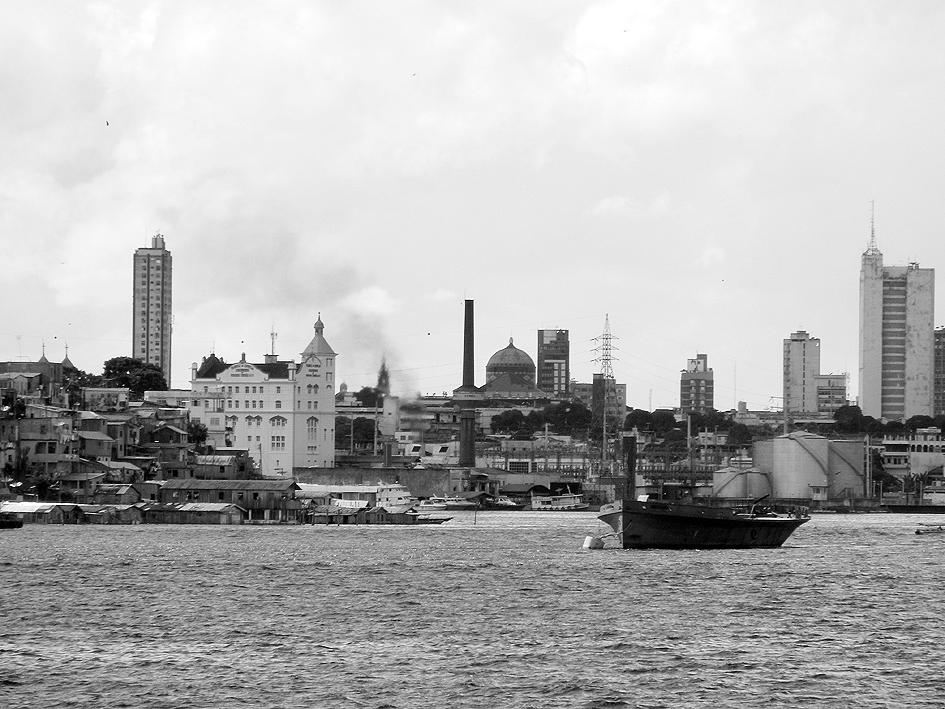Vista da cidade de Manaus a partir do grande rio: ao centro da skyline, vê-se a cúpula do Teatro Amazonas, símbolo da cultura européia e poderio econômico da elite urbana do século XIX, advindo dos seringais. Imagem: © Silvio Luiz Cordeiro.