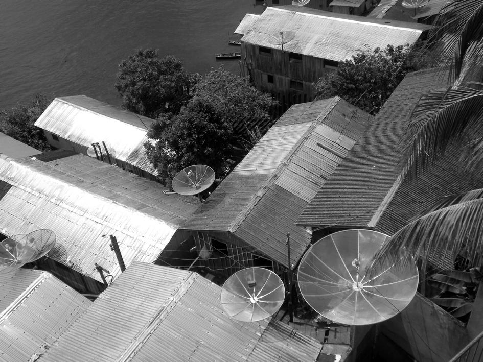 Vista de uma parte do casario na cidade de Tefé, sobre um barranco à margem esquerda do Solimões. Não há estradas. Chega-se à cidade, como tantas outras na região, por vias fluviais ou aéreas. As antenas instaladas nas casas captam imagens e imaginários, difundidos nas telas de TV, principal meio de informação das comunidades, ao lado do rádio e mesmo da Internet, em algumas delas. Imagem: © Silvio Luiz Cordeiro.